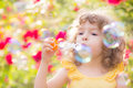 Picture : Kid blowing soap bubbles park of puppy