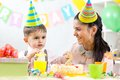 Kid boy celebrating birthday holiday. Mom looking Royalty Free Stock Photo