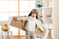 Kid boy dressed as pilot or aviator plays with handmade paper wings in his room Royalty Free Stock Photo