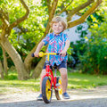 Kid boy driving tricycle or bicycle in garden Royalty Free Stock Photo