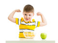 Kid boy eating healthy food and showing strength Royalty Free Stock Image