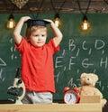 Kid boy in graduate cap ready to go to school, chalkboard on background. Kindergarten graduation concept. First former