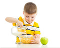Kid boy preparing corn flakes with milk Stock Photos