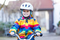 Kid boy in safety helmet and colorful raincoat riding bike, outd Royalty Free Stock Photo