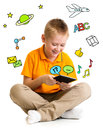 Kid boy sitting with tablet computer and learning or playing great interest Royalty Free Stock Image
