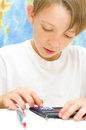 Kid with a calculator little schoolboy working for his maths subject in front of world map Royalty Free Stock Photo