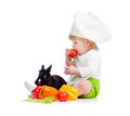 Kid in chef hat with healthy food and rabbit Stock Image