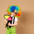 Kid in clown wig and eyeglasses playing catch ball game Royalty Free Stock Photo