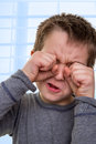 Kid crying with hands on his face eight years old while are touching eyes something very sad for him Royalty Free Stock Image