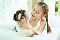 Kid with dog portrait of happy girl holding shih tzu and looking at it Royalty Free Stock Photos