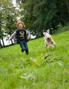 Kid and dog running picture of a happy young boy his labradoodle together over a green meadow Royalty Free Stock Image