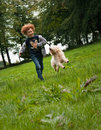 Kid and dog running picture of a young boy his labradoodle together over a green meadow the is making contact with the low Stock Photo