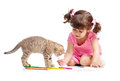 Kid drawing with pencils. Kitten next to girl. Stock Images