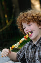 Kid eating fruit skewer young boy enjoying a healthy with at an outdoor barbecue Stock Photography