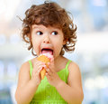 Kid eating ice cream. Funy curly child with icecream on blurred background. Royalty Free Stock Photo