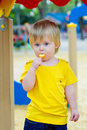 Kid eating lolly pop on the playground adorable little boy in yellow t shirt lollly Stock Photo