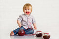 Kid eating strawberry jam adorable little boy got messy from glass jars Stock Photo