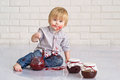 Kid eating strawberry jam funny little boy got messy from glass jars Royalty Free Stock Image