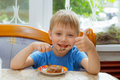 Kid eats cake dessert spoon at the table in the kitchen Royalty Free Stock Photo