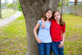 Kid friend girls whispering ear playing in a park tree children hug relaxed happy smiling outdoor Stock Photo