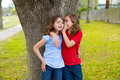 Kid friend girls whispering ear playing in a park tree children smiling outdoor Royalty Free Stock Images