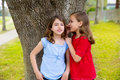 Kid friend girls whispering ear playing in a park tree children smiling outdoor Royalty Free Stock Image