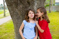 Kid friend girls whispering ear playing in a park tree children smiling outdoor Stock Images