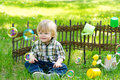 Kid in the garden and soap bubbles nice sitting on green grass by lath fence surrounded with Royalty Free Stock Images