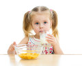 Kid girl eating corn flakes milk over white Royalty Free Stock Photo