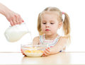 Kid girl eating corn flakes with milk over white Stock Photos