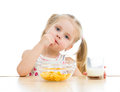Kid girl eating corn flakes with milk studio shot Royalty Free Stock Images
