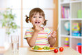 Kid girl eating healthy vegetables happy food at home Royalty Free Stock Photos
