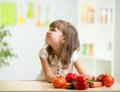 Kid girl with expression of disgust against child vegetables Stock Photography