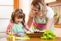 Kid girl with mom cooking fish in the kitchen Royalty Free Stock Photo