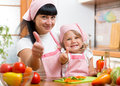 Kid girl and mother cooking and showing thumb up child Stock Photo