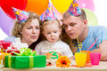 Kid girl with parents blow birthday candles Stock Photography
