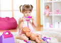 Kid girl playing the doctor with her newborn baby Royalty Free Stock Photo