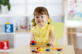Kid girl playing with logical toy on desk in nursery room or kindergarten. Child arranging and sorting colors and sizes Royalty Free Stock Photo