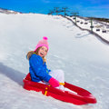Kid girl playing sled in winter snow Stock Images