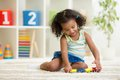 Kid girl playing toys at kindergarten room