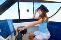 Kid girl pretending be a captain sailor cap in boat Royalty Free Stock Photo