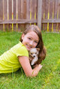 Kid girl and puppy dog happy lying in lawn playing with chiuahua pet backyard Stock Photo