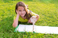 Kid girl and puppy dog at homework lying in lawn doing with chiuahua pets backyard Royalty Free Stock Image