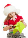 Kid girl in Santa Claus hat cutting paper tree Royalty Free Stock Images