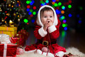 Kid girl Santa Claus near Christmas tree Royalty Free Stock Photo