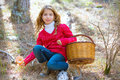 Kid girl searching chanterelles mushrooms with basket in autumn Royalty Free Stock Photo