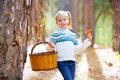 Kid girl searching chanterelles mushrooms with basket in autumn forest Royalty Free Stock Images