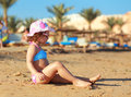 Kid girl sitting on the beach sand and sunbathing Royalty Free Stock Images