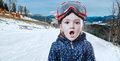 Kid girl in ski gear on winter background Royalty Free Stock Photo
