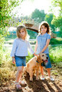 Kid girls with Golden retriever puppy outdoor Stock Image